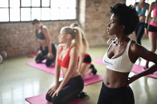 selective focus photography of woman in white sports brassiere standing near woman sitting on pink yoga mat